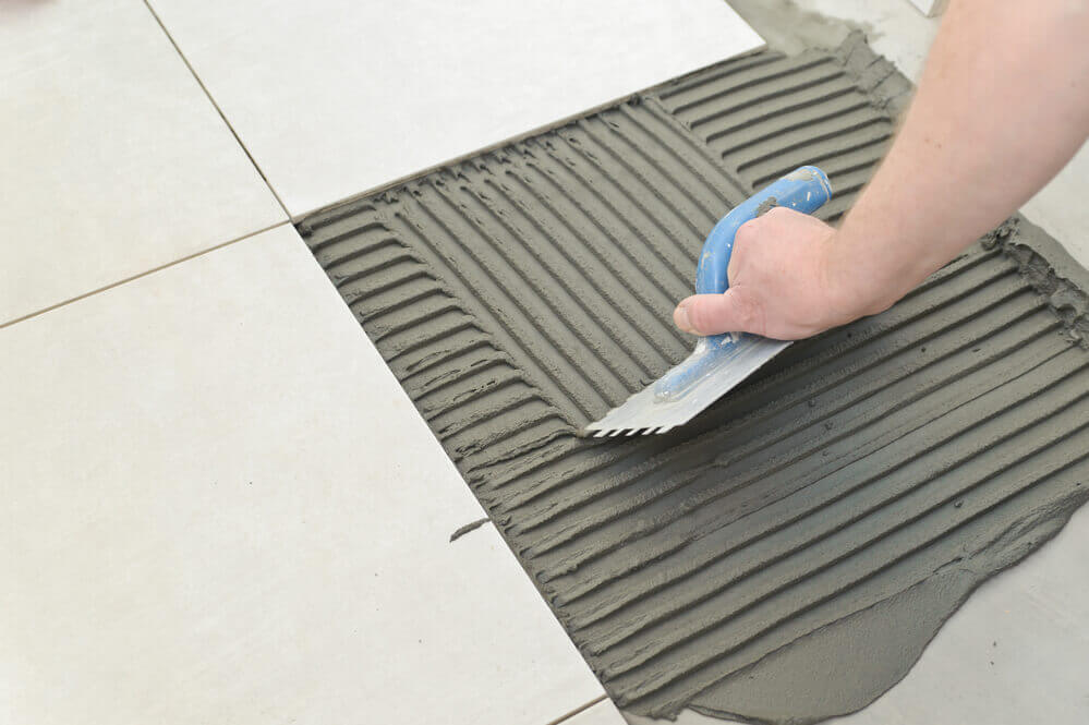 Close up of a tiler putting down the ground and ready to lay down the floor tiles